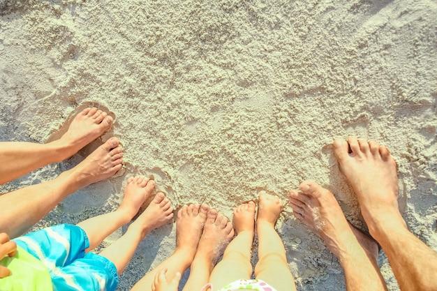 Rodzinne nogi na piasku nad morzem