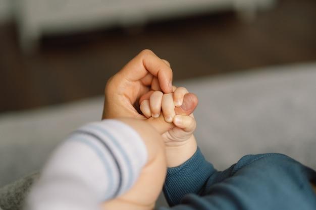 Rodzinne ręce dziecka. zbliżenie dłoni dziecka w ręce matki. matka trzyma noworodka. koncepcja rodziny.