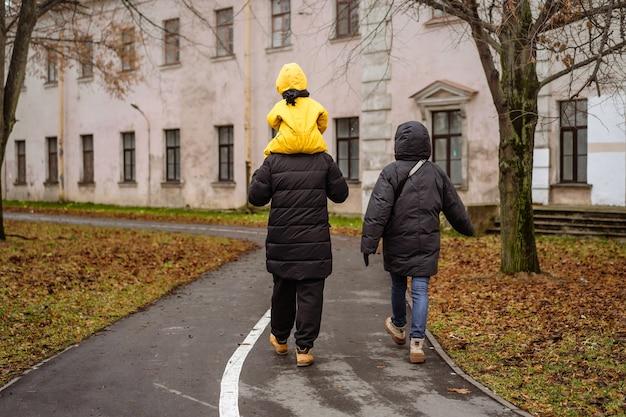 Rodzinne spacery po parku. ojciec nosi na ramionach dziecko w żółtym kombinezonie