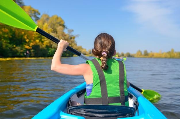 Rodzinne spływy kajakowe, dziecko wiosłujące w kajaku na wycieczce kajakiem po rzece, dzieciak w aktywny jesienny weekend i wakacje