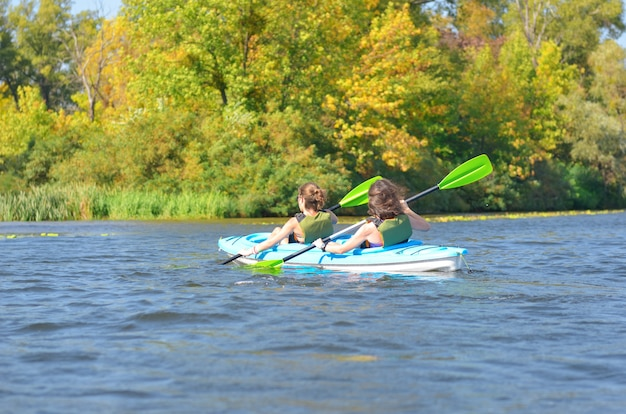 Rodzinne spływy kajakowe, matka i córka wiosłują w kajaku na wycieczce kajakiem po rzece bawiąc się, aktywny jesienny weekend i wakacje z dziećmi, fitness