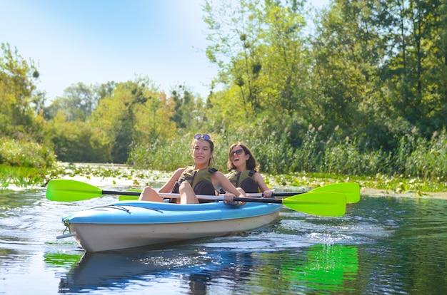 Rodzinne spływy kajakowe, matka i córka wiosłują w kajaku na wycieczce kajakiem po rzece, bawiąc się, aktywny jesienny weekend i wakacje z dziećmi, koncepcja fitness