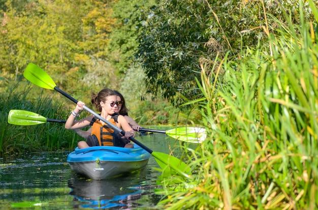 Rodzinne spływy kajakowe, matka i córka wiosłują w kajaku na wycieczce kajakiem po rzece