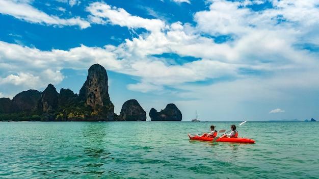 Rodzinne spływy kajakowe, matka i córka wiosłują w kajaku podczas tropikalnej wycieczki kajakiem po wyspach, bawiąc się, aktywnie spędzając wakacje z dziećmi w tajlandii, krabi