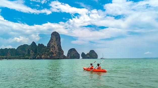 Rodzinne spływy kajakowe po morzu, matka i córka brodzący w kajaku na tropikalnej wycieczce kajakiem po morzu w pobliżu wysp, dobra zabawa, aktywny wypoczynek z dziećmi w tajlandii, krabi