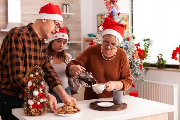 Rodzinne świętowanie bożego narodzenia razem w boże narodzenie udekorowanej kuchni kulinarnej