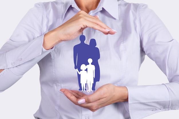 Rodzinne ubezpieczenia na życie, usługi rodzinne i koncepcje wspierania rodzin. businesswoman z ochronnym gestem i sylwetką reprezentującą młodą rodzinę. zdjęcie wysokiej jakości