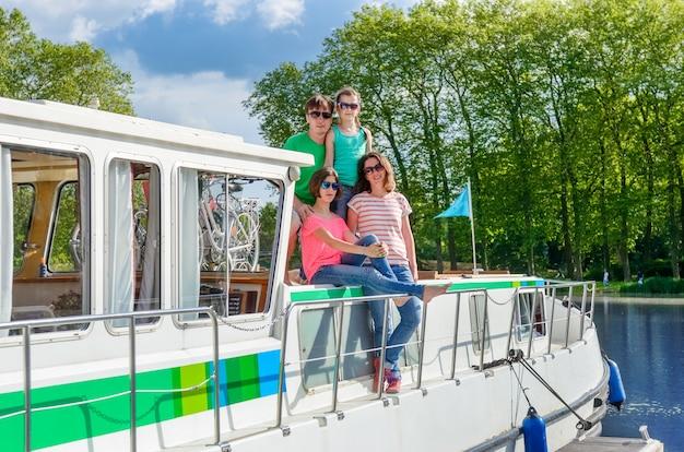 Rodzinne wakacje, letnie wakacje na barce w kanale, szczęśliwe dzieci i rodzice bawią się na rejs po rzece w łodzi mieszkalnej we francji