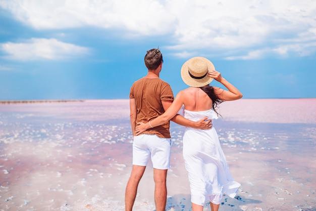 Rodzinne wakacje. młoda para spędza wakacje na plaży z niesamowitym widokiem na różowe słone jezioro