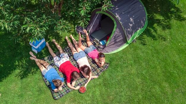 Rodzinne wakacje na campingu z lotu ptaka z góry, rodzice i dzieci odpoczywają i bawią się w parku, namiocie i sprzęcie kempingowym pod drzewem, rodzina w obozie na świeżym powietrzu koncepcja