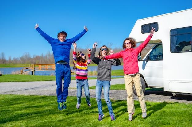 Rodzinne wakacje, podróż samochodem rv z dziećmi, szczęśliwi rodzice z dziećmi bawią się podczas wakacyjnej podróży samochodem kempingowym, na zewnątrz kampera