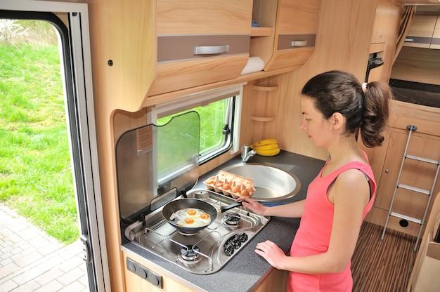 Rodzinne wakacje, rv trip, podróże i camping, szczęśliwa uśmiechnięta kobieta gotująca w kamperze, wnętrze kampera