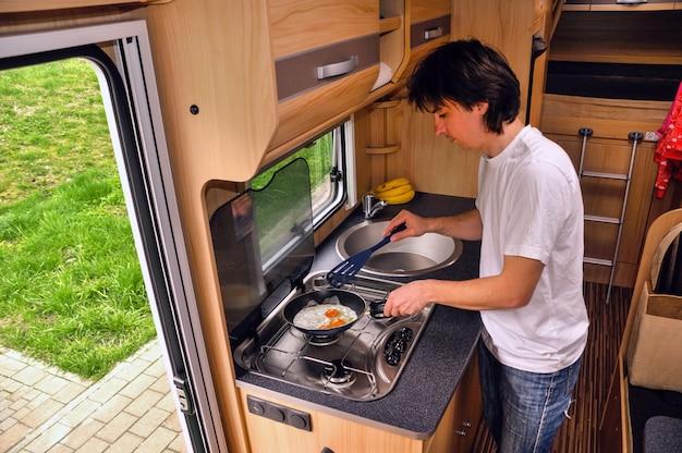 Rodzinne wakacje, wycieczka samochodem kempingowym, człowiek gotujący w kamperu. wnętrze kampera