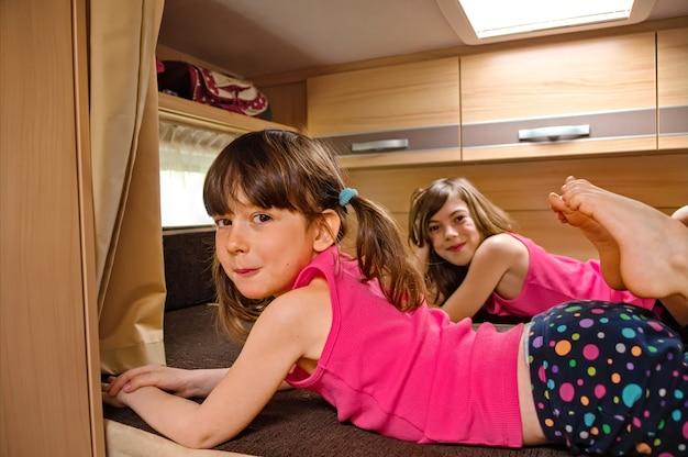 Rodzinne wakacje, wycieczka samochodem kempingowym, kemping, szczęśliwe uśmiechnięte dzieci podróżują na kamperze, dzieci w samochodzie kempingowym