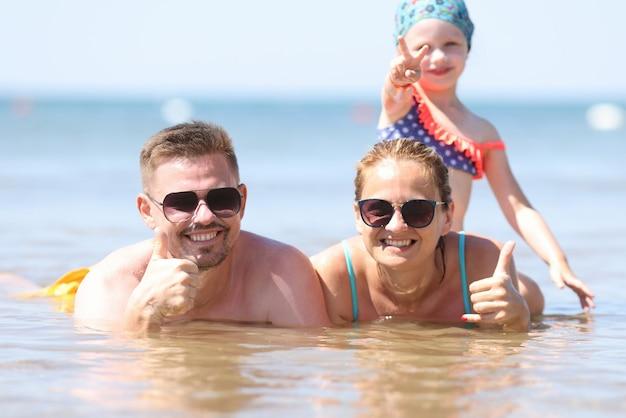 Rodzinne wakacje z dziećmi na morzu. mężczyzna i kobieta w okularach przeciwsłonecznych leżą w wodzie i pokazują kciuki do góry. dziewczyna siedzi na matce i pokazuje dwa palce.