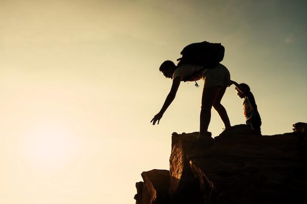 Rodzinne wędrówki na szczyt o zachodzie słońca. koncepcja pomocy