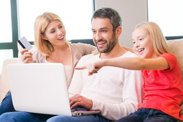 Rodzinne zakupy online. szczęśliwa trzyosobowa rodzina, która łączy się ze sobą i uśmiecha, siedząc na kanapie i robiąc wspólne zakupy online