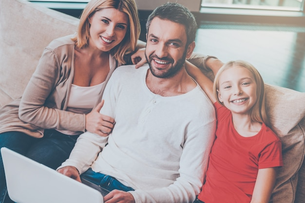Rodzinne zakupy online. widok z góry na szczęśliwą rodzinę trzech osób, które łączą się ze sobą i uśmiechają podczas wspólnego surfowania po sieci w domu