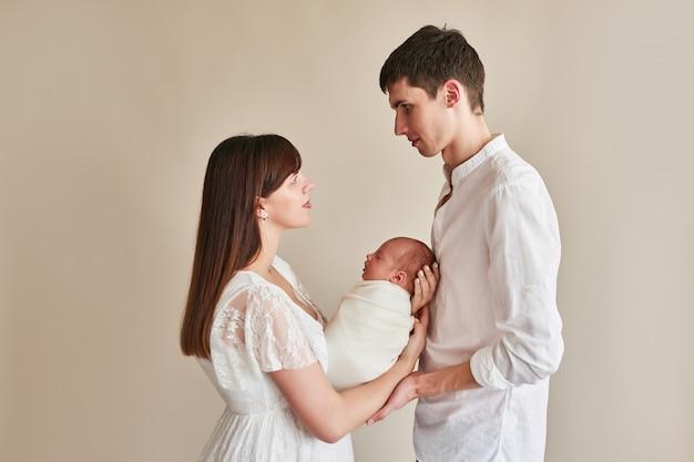 Rodzinni młodzi rodzice z nowonarodzonym domem
