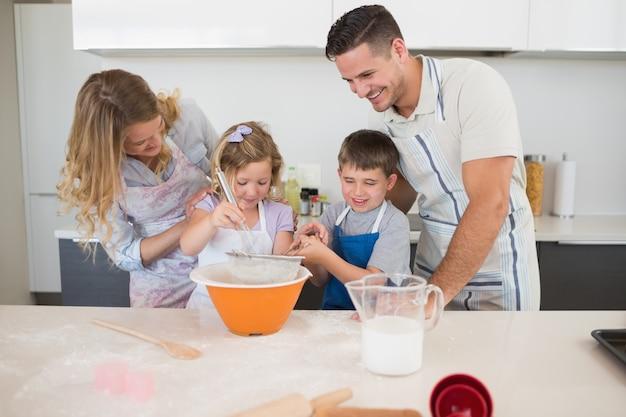 Rodzinni narządzań ciastka przy kuchennym kontuarem