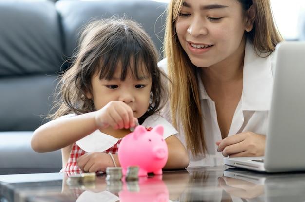 Rodzinny azjatykci oszczędzanie pieniądze w prosiątko banku. oszczędzać pieniądze