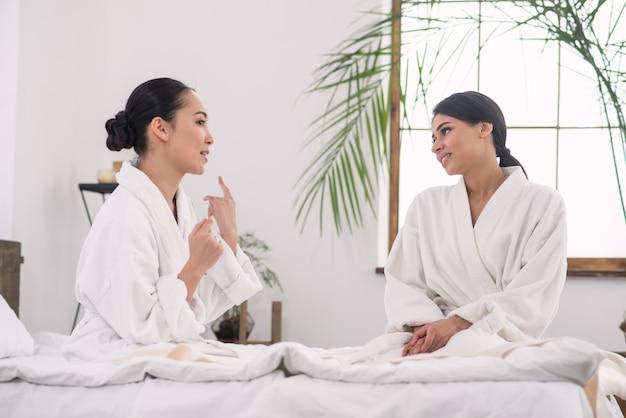 Rodzinny dzień. pozytywne młode siostry rozmawiające ze sobą w salonie spa