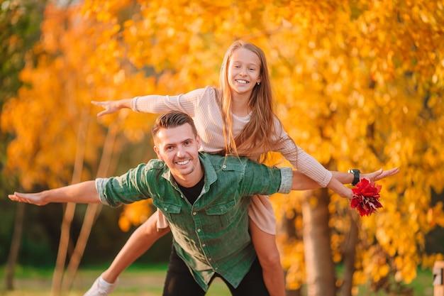Rodzinny jesienny weekend. młody ojciec i jego córeczka razem w jesiennym parku