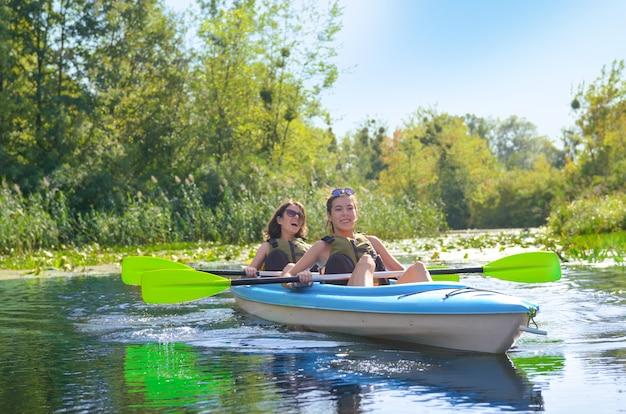 Rodzinny kajak, matka i dziecko wiosłują w kajaku na wycieczce kajakiem po rzece, aktywny letni weekend i wakacje, koncepcja sportu i fitnessu