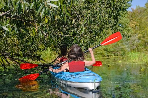 Rodzinny kajak, matka i dziecko wiosłują w kajaku na wycieczce kajakiem po rzece, aktywny letni weekend i wakacje, sport i fitness