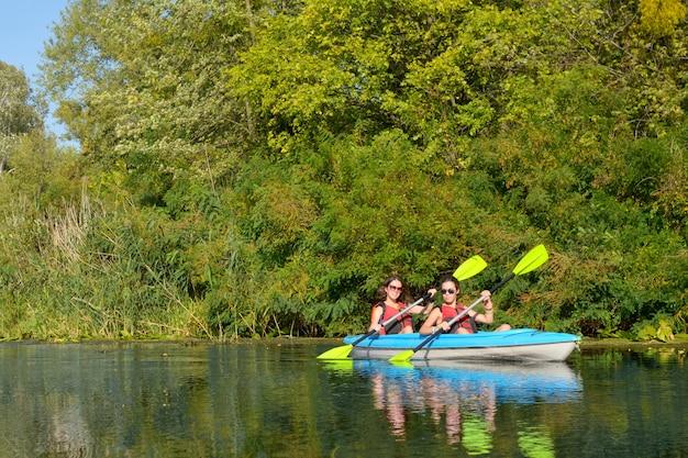 Rodzinny kajak, matka i dziecko wiosłują w kajaku na wycieczce kajakiem po rzece, aktywny weekend jesienny i wakacje, koncepcja sportu i fitnessu