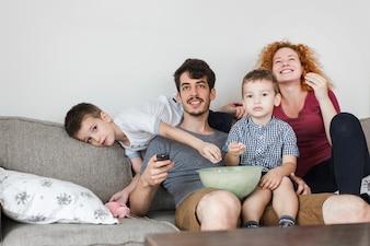 Rodzinny obsiadanie na kanapie ogląda telewizję w domu
