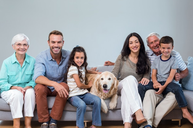 Rodzinny obsiadanie na kanapie z psem