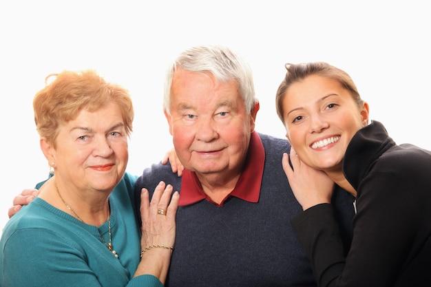 Rodzinny portret dziadków z wnuczką stojącą i uśmiechającą się na białym tle