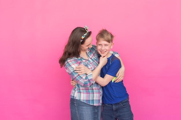 Rodzinny portret siostry i nastolatka brat na różowej ścianie