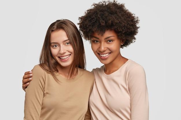 Rodzinny portret szczęśliwych sióstr rasy mieszanej przytulają się, mają zadowolone miny