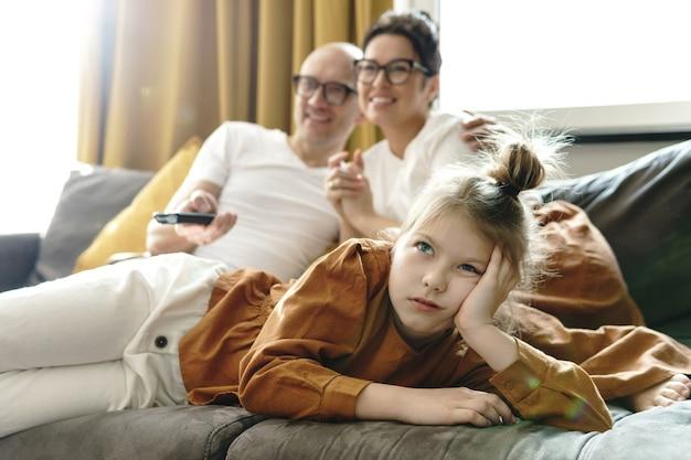 Rodzinny relaks w domu. znudzona dziewczynka nie lubi programów telewizyjnych dla dorosłych.