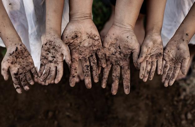Rodzinny rodzic i dzieci pokazuje brudne ręce po posadzeniu drzewa razem w ogrodzie