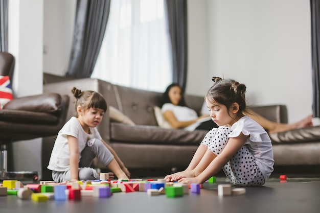 Rodzinny smutny dziewczyny obsiadanie na podłoga, jej siostra bawić się zabawki i matka patrzeje jej córki wpólnie.