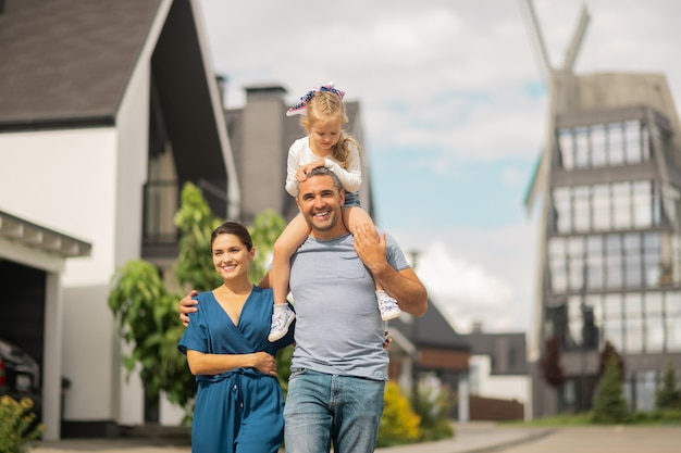 Rodzinny spacer. urocza słodka córka siedzi na szyi ojca podczas rodzinnego spaceru