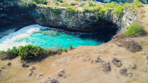 Rodzinny styl życia. ojciec, matka z dziećmi chodzą i wyglądają na naturalny basen morski broken bay. cel podróży na bali. nusa penida island day tour popularne miejsce. aktywność na wakacjach na plaży z dziećmi.
