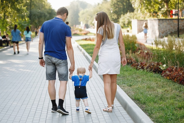 Rodzinny tata, mama i syn spacerują latem po chodniku w miejskim parku