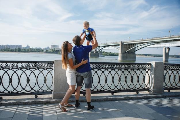 Rodzinny tata, mama i syn spacerują latem po nabrzeżu rzeki w mieście