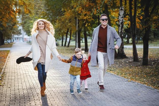 Rodzinny tata, mama, syn i córka biegną chodnikiem w parku. on jest w szarym płaszczu i czarnych okularach, ona jest w bieli, dziewczyna jest blondynką w czerwieni.