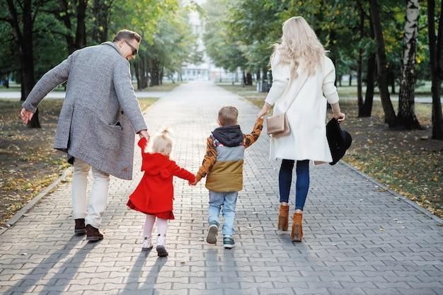 Rodzinny tata, mama, syn i córka biegną chodnikiem w parku.