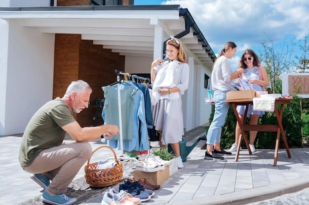 Rodzinny weekend. czterech członków dużej, szczęśliwej rodziny czuje się radośnie i niezapomniany podczas weekendowej wyprzedaży na podwórku