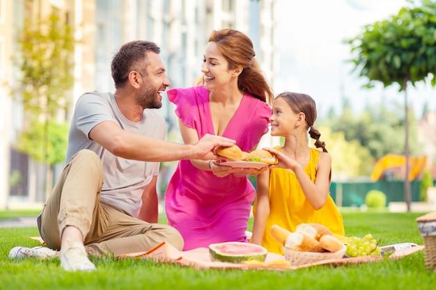 Rodzinny weekend. szczęśliwa radosna rodzina siedzi razem podczas pikniku