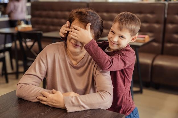Rodzinny wypoczynek i rozrywka. szczęśliwa babcia z krótkimi włosami, okularami i wnukiem odpoczywa w kawiarni. dziecko przytula babcię i zamyka oczy własnymi rękami