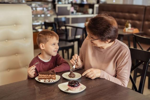 Rodzinny wypoczynek i rozrywka. szczęśliwa babcia z krótkimi włosami, okularami i wnukiem odpoczywa w kawiarni. jedzą ciasta z koktajlami mlecznymi