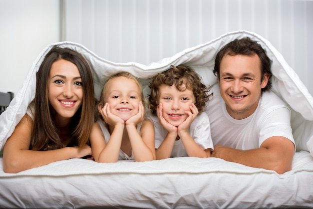 Rodziny z dziećmi w łóżku pod kocem.