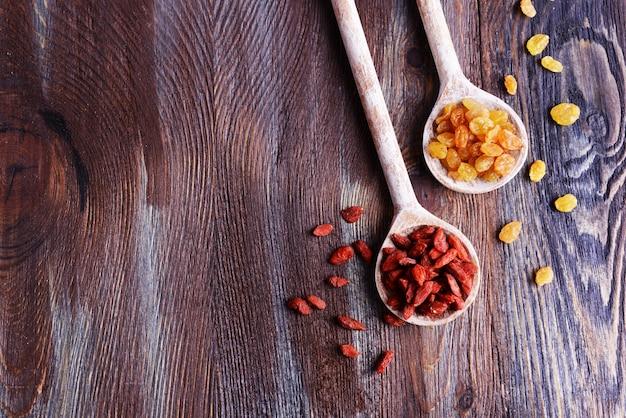 Rodzynki i goji w łyżkach na tle rustykalnym drewnianym stole